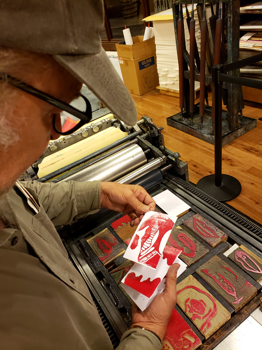 man holding prints from press